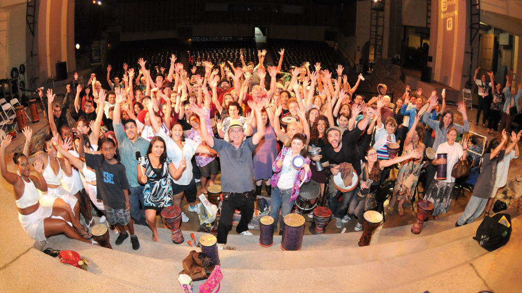 Group shot of people with hands in the air rejoicing after a wonderful drum session